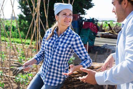 Female gardener friendly talking to neighbour on farm backyard