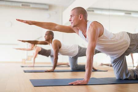 Man practicing Dandayamna Bharmanasana during group yoga training