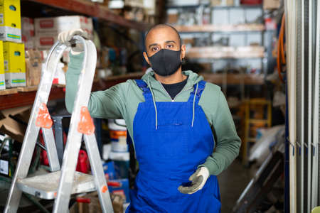 Worker of building materials store in protective mask near stepladder Banque d'images