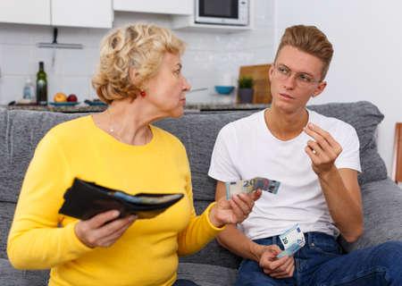 Mature woman giving pocket money son