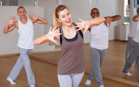 Cheerful woman practicing vigorous movements in group dance class