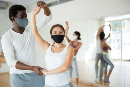 Couple in masks learning to dance waltz during group training