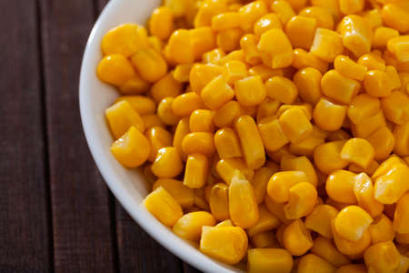 Grains boiled corn on plate on wooden table. Vegetarian ingredient