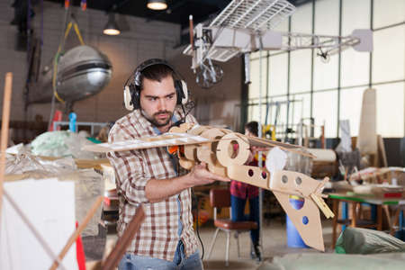 Male creating airplane models