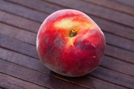 Closeup of whole ripe red peaches on wooden table.