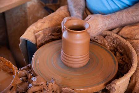 Man sculpting ceramics on potters wheel