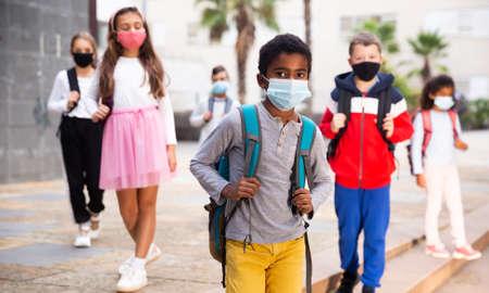 Schoolboy in medical mask standing near school, kids on background Stockfoto