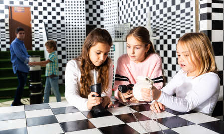 Tween girls solving conundrum in quest room stylized under chessboard