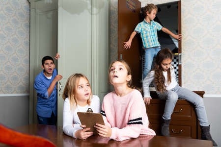 Two preteen girls trying to find solution of riddles in quest room Stock Photo