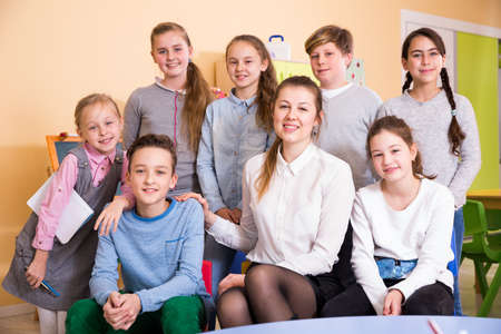 Friendly group of pupils with teacher in schoolroom