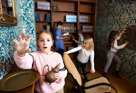 Tween girl trying to reach for something in escape room Stock Photo