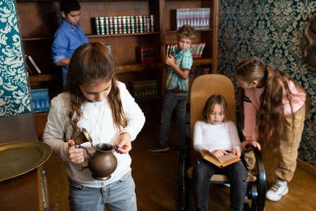 Tween girl examining ancient kettle in quest room