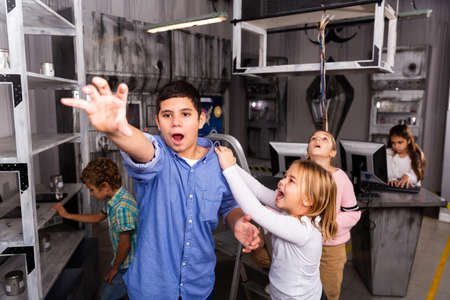 Little girl yelling at boy reaching for something in quest room bunker