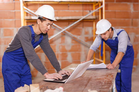 Professional builders using laptop