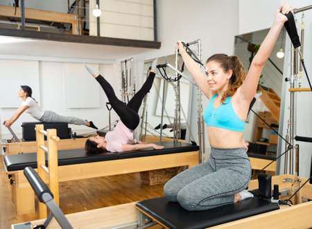 Young woman practicing pilates exercises on reformer at gym Reklamní fotografie