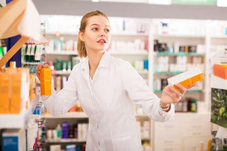 Pharmacist offering medicine in pharmacy