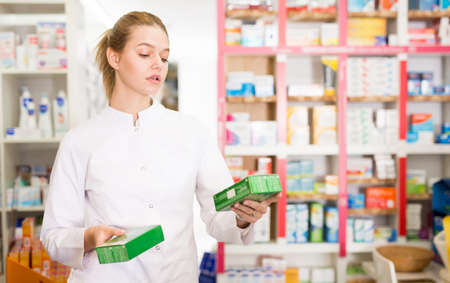 Young friendly female pharmacist suggesting useful tablets in pharmacy Foto de archivo
