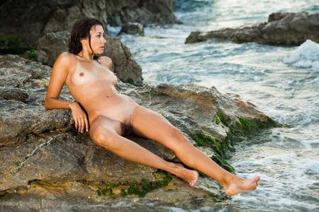 Nakrd slender woman posing on rock Stock fotó