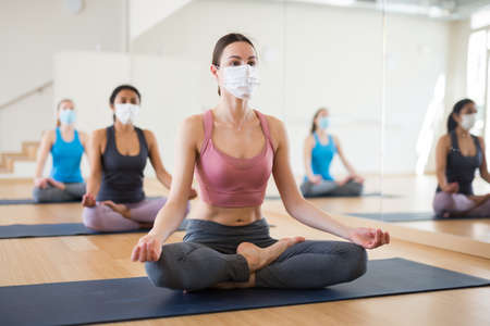 Girl in protective mask sitting in lotus positions during group yoga training