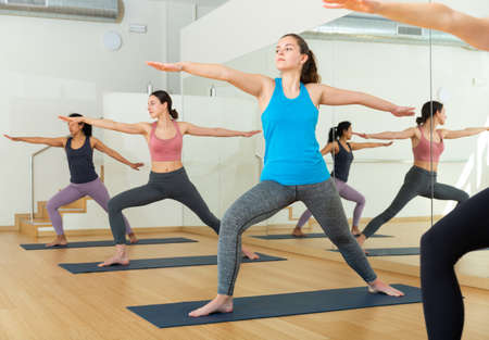 Girl practicing Virabhadrasana during group yoga training Standard-Bild