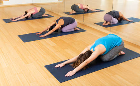 Sporty females doing stretching workout during group training