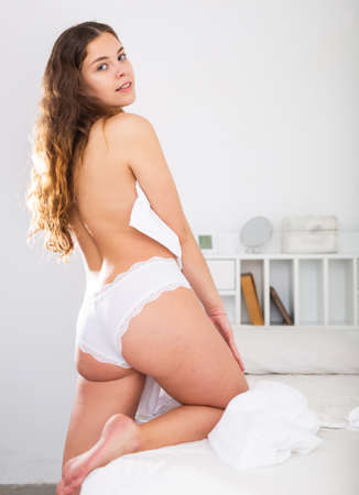 Girl in white panties covering with bedsheet near bed