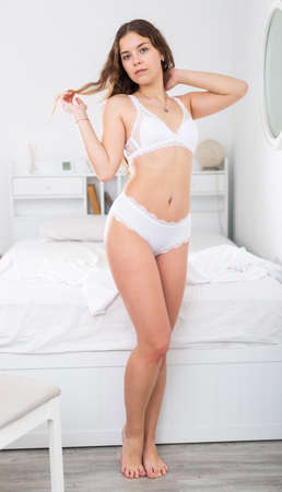 Flirtatious girl in white lingerie standing near bed