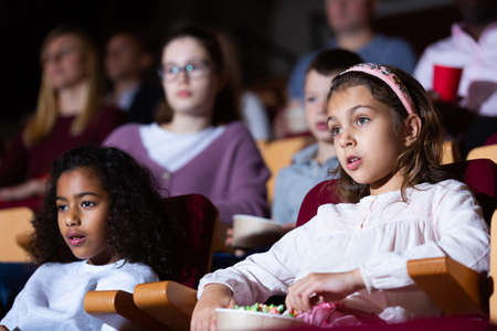 kids sitting at movie in auditorium in cinema