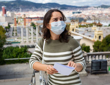 Girl traveler in protective mask with a guidebook in her hands on the street of european city