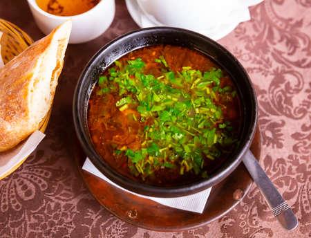 Georgian kharcho soup with lamb garnished with fresh greens Foto de archivo