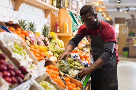 Salesman filling counter with vegetables and fruits