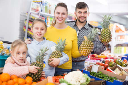 family with pineapples during family shopping Foto de archivo