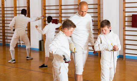 Coach demonstrating fencing movements to kids Foto de archivo