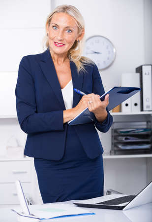Female assistant with clipboard noting tasks