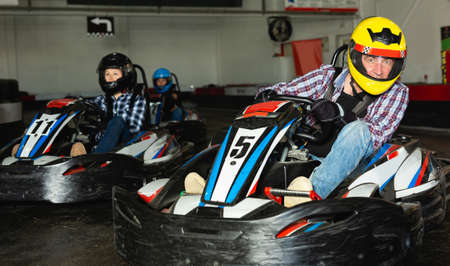 Man and women competing on racing cars