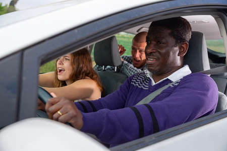 Frightened african american driving car with scared passengers