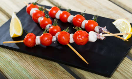 Grilled mini-squid with cherry tomatoes Imagens