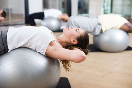 Girl exercising with pilates ball during group class
