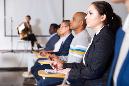 Focused woman listening to lecture at conference
