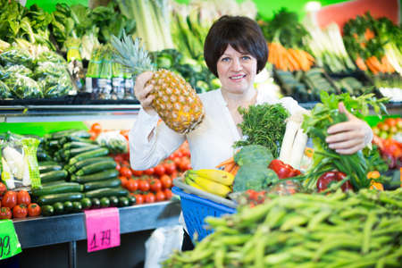 Middle aged woman with basket choosing fruits