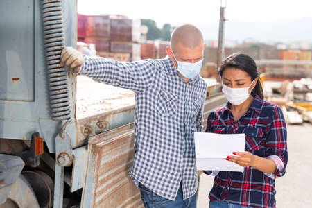 Manager in protective mask gives instructions to the car driver at building materials storage site