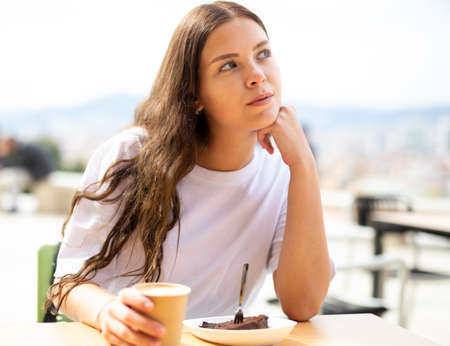 Portrait of a thoughtful girl sitting at a table with a cup of coffee