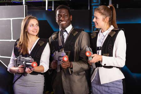 African man and young women holding laser guns Banco de Imagens