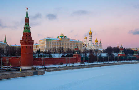 Moscow Kremlin on bank of snow covered Moskva River at sunset