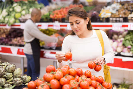 Latin woman choosing red tomatoes in supermarket
