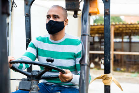 man with protective mask working in forklift Stock Photo