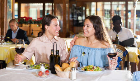 Two best friends have fun talking at a table in restaurant