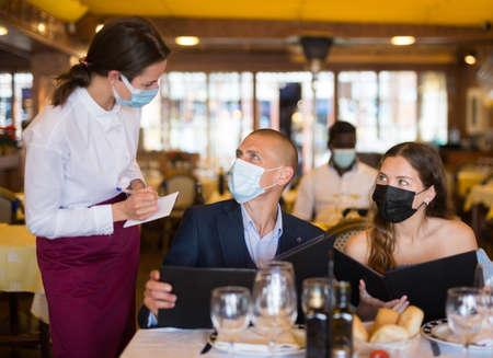 Positive young couple making order at restaurant