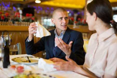 Young couple man and woman quarreling in restaurant