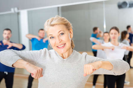 Middle-aged woman exercising at dance class